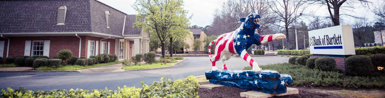 Outside shot of a Bank of Bartlett location. There is a red, white, and blue tiger sculpture in the foreground.