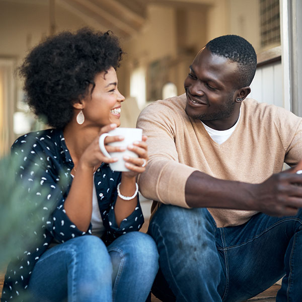 Couple smiling at each other and holding mugs