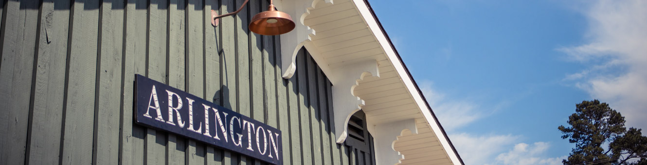 "Close up of a blue sign on top of a wooden building that reads, ""ARLINGTON"""
