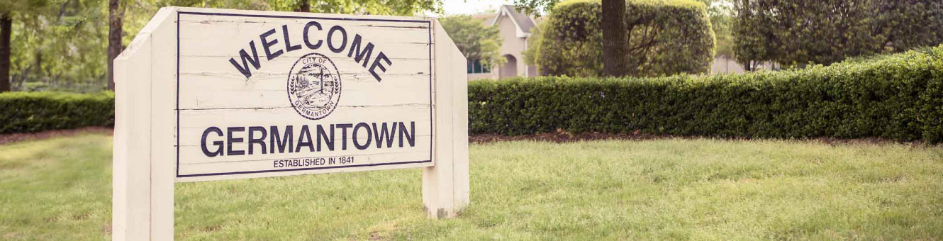 "A white wooden sign that reads ""Welcome to Germantown"""