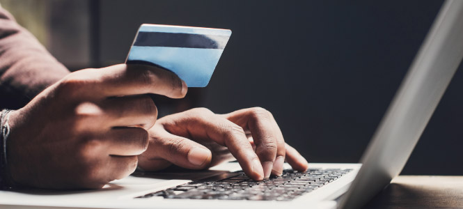 Close up of a person's hands, one is holding a credit card while the other is typing on a laptop keyboard