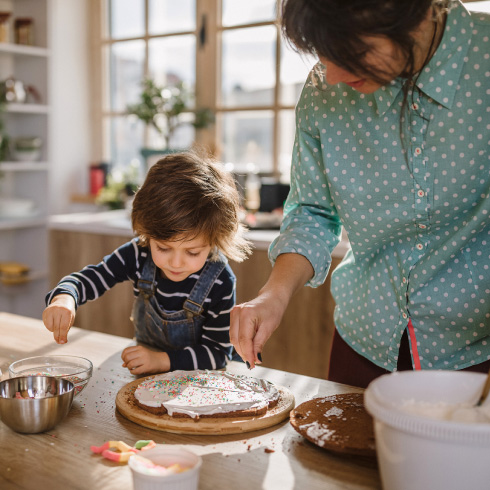 A mom and her young child decorating a cake in a modern kitchen.