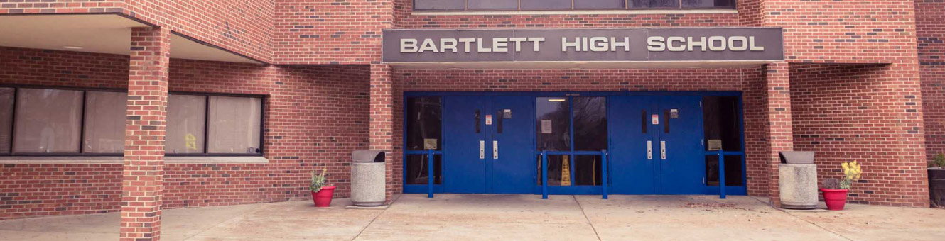 "The front of a large brick building with blue doors. Text above the doors read, ""Bartlett High School"""