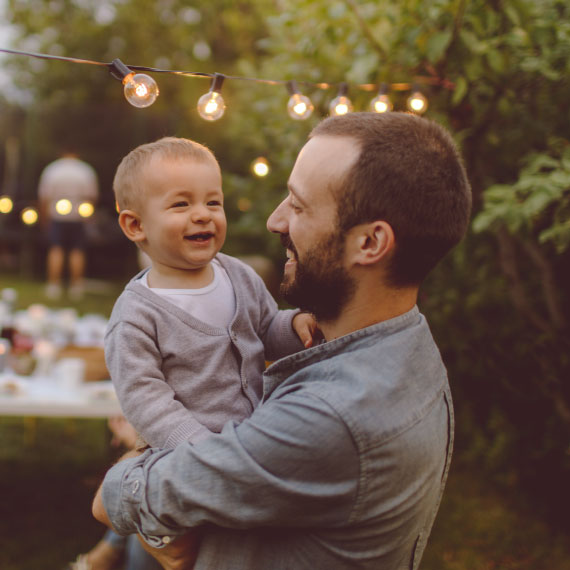 a man holding his child while laughing