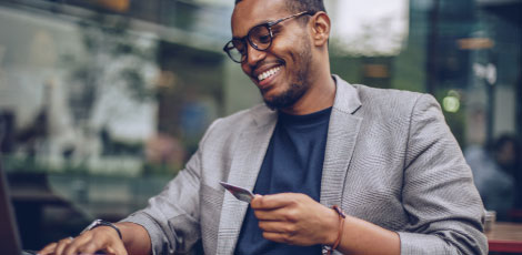 A man who is smiling and holding a credit card.