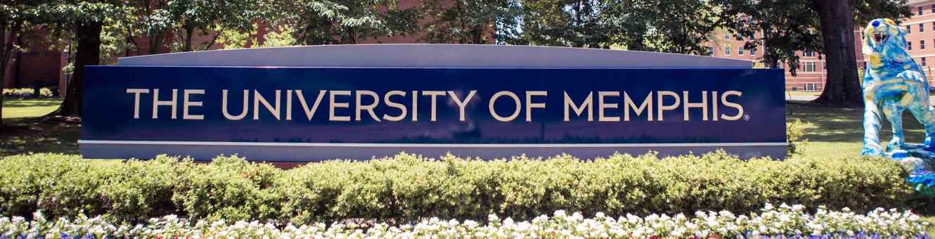 "Wide shot of a blue sign that says ""The University of Memphis"" with a blue tiger next to the sign"