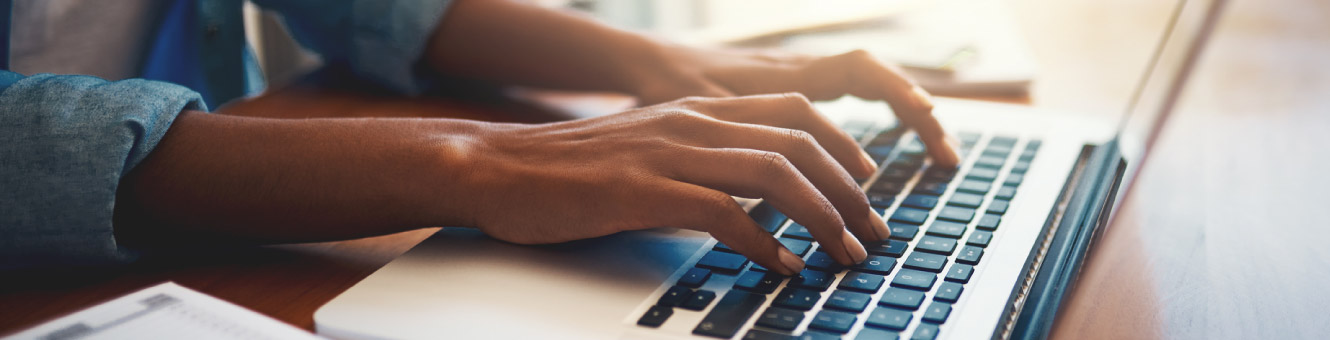 Close up of a person's hands typing on a laptop keyboard